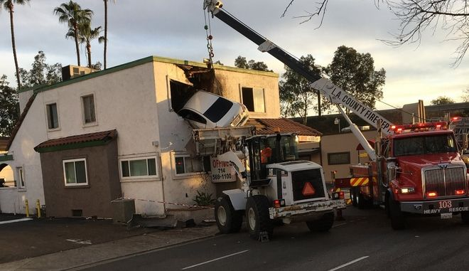 In this Sunday, Jan. 14, 2018, photo provided by Orange County Fire Authorit, a vehicle that crashed into a building hangs from a second story window in Santa Ana, Calif. Members from Orange County Fire Authority and Los Angeles County Urban Search & Rescue rescued two people, who escaped serious injuries when the car they were in went airborne and slammed into the second floor of a dental office in Southern California. Authorities say the Nissan Altima hit a center divider early Sunday, soared into the air and plowed into the top floor of the two-story structure. (Capt. Stephen Horner /Orange County Fire Authority via AP)