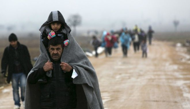 A migrant carrying a child covered with a blanket, walks from the Macedonian border into Serbia, near the village of Miratovac, Serbia, Wednesday, Jan. 6, 2016. Hundreds of migrants continue to arrive daily into Serbia in order to register and continue their journey further north towards Western Europe. (AP Photo/Visar Kryeziu)