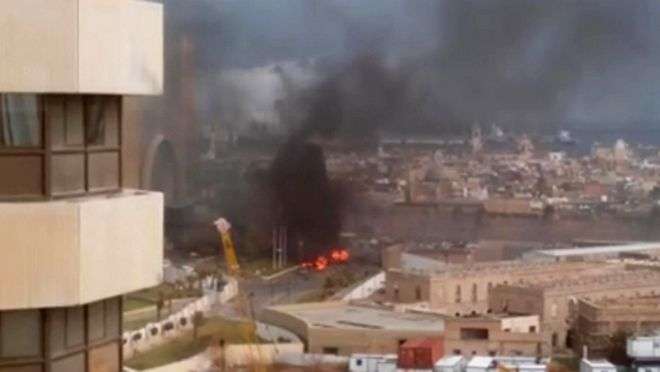 FILE - In this file image made from video posted by a Libyan blogger, the Cortinthia Hotel is seen under attack in Tripoli, Libya, Tuesday, Jan. 27, 2015. The blogger, @AliTweel, captured the moments shortly after the blast, when flames rose up from outside the hotel, appearing to be from the aftermath of the car bomb. A group affiliated with the extremist Islamic State claims a deadly and fairly complex attack on a Tripoli hotel _ indicating an expansion of the groups activities to a chaotic North African state on the cusp of Europe and suggesting a level of coordination with its core in Syria and Iraq. (AP Photo/ @AliTweel via AP video, File)