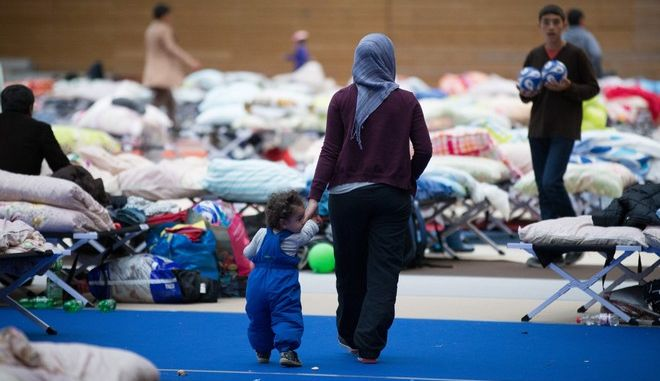 In this Saturday Sept. 12, 2015 picture refugees and migrants  walk in a sports hall  in Berlin that was turned into a asylum-seeker accommodation . ( Kay Nietfeld/dpa via AP)
