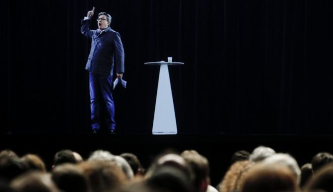 The hologram of hard-left French presidential candidate Jean-Luc Melenchon speaks to supporters who are gathered in Saint-Denis, near Paris, Sunday, Feb. 5, 2017. As Melenchon holds a rally in Lyon Sunday, a hologram of him is being projected by satellite to crowds in Paris. (AP Photo/Kamil Zihnioglu)