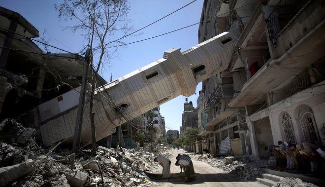 Παλαιστίνιοι προσεύχονται μπροστά σε κατεστραμμένο από τις ισραηλινές επιδρομές μιναρέ τζαμιού