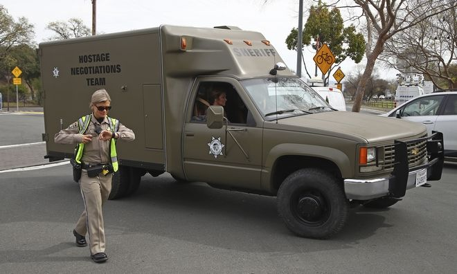 A sheriff's hostage negotiation team passes a California highway patrol checkpoint at the Veterans Home of California in Yountville, Calif., Friday, March 9, 2018. Napa County Fire Capt. Chase Beckman says a gunman has taken hostages at the veterans home. Police closed access to the large veterans home after a man with a gun was reported on the grounds. (AP Photo/Ben Margot)