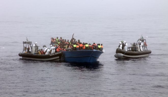 In this picture taken on June 6, 2015 and made available on Monday, June 8, 2015, provided by Irish Defence Forces, officers of the Irish Navy ship Le Eithne rescue migrants in the Mediterranean Sea. Heartened by recent election successes by an anti-immigrant party, Italian politicians based in the north vowed Sunday not to shelter any more migrants saved at sea, even as thousands more were being rescued in the Mediterranean from smugglers' boats in distress. (Irish Defence Forces via AP)