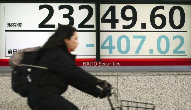 Γυναίκα με ποδήλατο μπροστά από ηλεκτρονικό πίνακα συναλλαγών