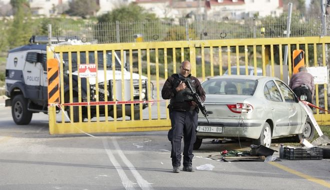 Israeli security stands around a car involved in an attack at the entrance of Carmei Tzur settlement in the West Bank, Wednesday, Feb. 7, 2018. A security guard shot dead a Palestinian attacker after he stabbed another guard, military said. (AP Photo/Mahmoud Illean)