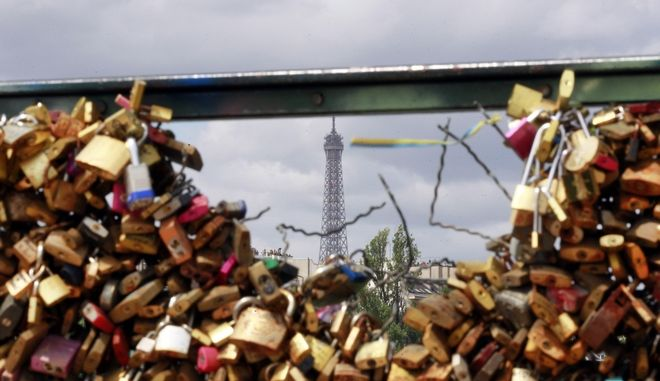 The Eiffel tower appears through the partly lock-free railing of the famed Pont des Arts bridge in Paris, Monday June 1, 2015. Lovers in Paris, beware: City authorities are taking down thousands of padlocks affixed to the famed Pont des Arts bridge. The city council says the locks, usually hung by couples to express eternal love, cause long-term damage to Paris heritage and sometimes pose a security risk. Last summer a chunk of fencing fell off under their weight. (AP Photo/Remy de la Mauviniere)
