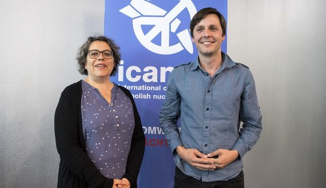 """Sascha Hach, right, and Xanthe Hall of the International Campaign to Abolish Nuclear Weapons  ICAN  Germany, pose in their office in Berlin, Friday, Oct. 6, 2017. The International Campaign to Abolish Nuclear Weapons (ICAN) is the winner of this year's Nobel Peace Prize. The Norwegian Nobel Committee honored the Geneva-based group """"for its work to draw attention to the catastrophic humanitarian consequences of any use of nuclear weapons and for its ground-breaking efforts to achieve a treaty-based prohibition of such weapons."""" (Bernd von Jutrczenka/dpa via AP)"""