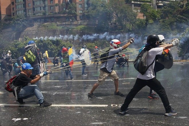 2017 AP YEAR END PHOTOS - Anti-government protesters work together to aim a giant slingshot holding a glass bottle of fecal matter, at security forces blocking their march from reaching the Supreme Court in Caracas, Venezuela, on May 10, 2017. (AP Photo/Ariana Cubillos)