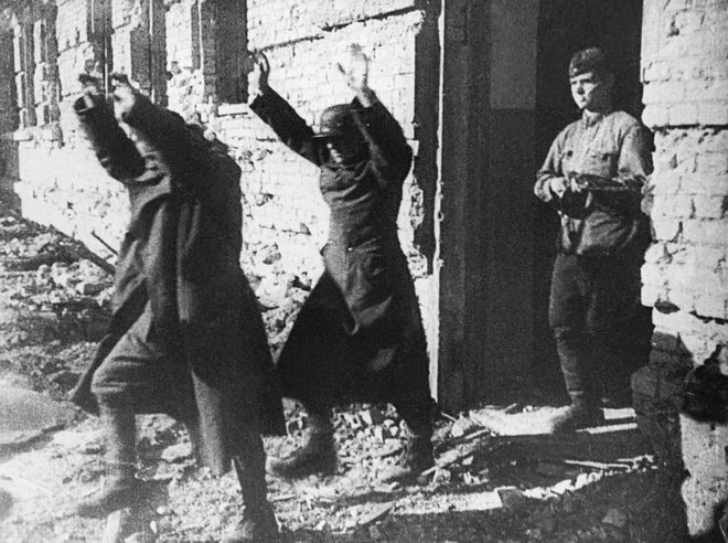 Eyes front, and hands up, two Axis soldiers march out of a battered building, followed by one of their Russian captors in Stalingrad on January 25, 1943. (AP Photo/Paramount News) **NO SALES**