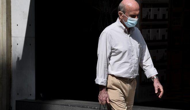 Άντρας με μάσκα περπατά στο κέντρο της Αθήνας