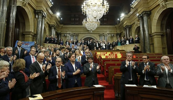 Catalan President Carles Puigdemont, bottom center, and others applaud after a vote on independence in the Catalan parliament in Barcelona, Spain, Friday, Oct. 27, 2017. Catalonia's regional parliament passed a motion with which they say they are establishing an independent Catalan Republic. (AP Photo/Manu Fernandez)