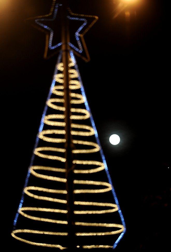 Η Πανσέληνος που φέτος συνέπεσε ανήμερα τα Χριστούγεννα,μοιάζει με ένα ακόμη στολίδι των χριστουγέννων στους δρόμους της Αθήνας,Παρασκευή 25 Δεκεμβρίου 2015