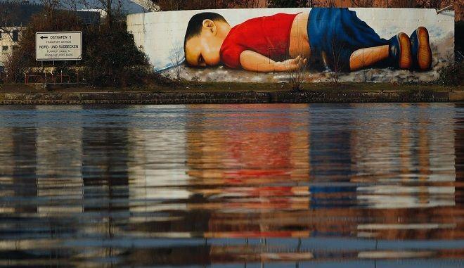 Για να μην ξεχάσουν ποτέ! Στη Φρανκφούρτη η εικόνα του 3χρονου Αιλάν που έκανε τον κόσμο να ανατριχιάσει