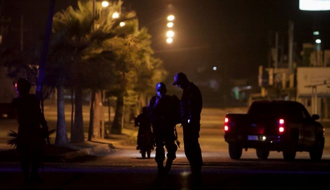 State police patrol a street near the place where two people were shot dead by unidentified attackers in Culiacan, Mexico, late Tuesday, Feb. 7, 2017. More persons have been killed in Sinaloa state hours after several suspects and a marine died during a clash in the city of Culiacan. (AP Photo/Rashide Frias)