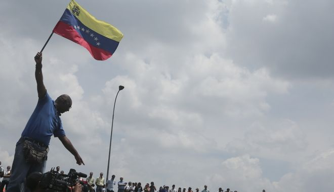 A man waves a Venezuelan national flag as anti-government protesters block a highway in Caracas, Venezuela, Monday, April 24, 2017. Opponents to President Nicolas Maduro shut down main roads around the country as the protest movement against the socialist administration is entering its fourth week. (AP Photo/Fernando Llano)