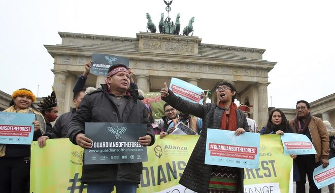 Indigenous leaders from 14 nations take part in a demonstration in front of the Brandenburg Gate in Berlin, Germany, Wednesday, Nov. 1, 2017. The indigenous leaders are in Berlin as part of a tour of European capitals to release new research in advance climate talks in the German former capital Bonn next week. (AP Photo/Michael Sohn)