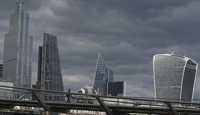 A man walks across the Millennium Bridge in London, Wednesday, May 13, 2020, as the country continues in lockdown to help stop the spread of coronavirus. Despite the relaxation of some of the coronavirus lockdown measures on Wednesday central London was still quite. (AP Photo/Tony Hicks)