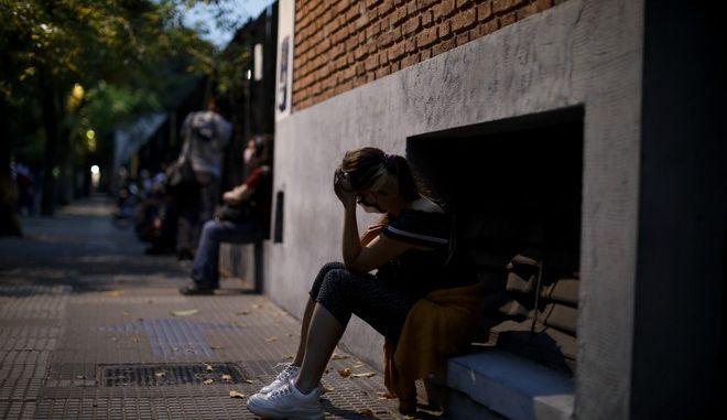 Γυναίκα με μάσκα στην Αργεντινή περιμένει να κάνει τεστ κορονοϊού