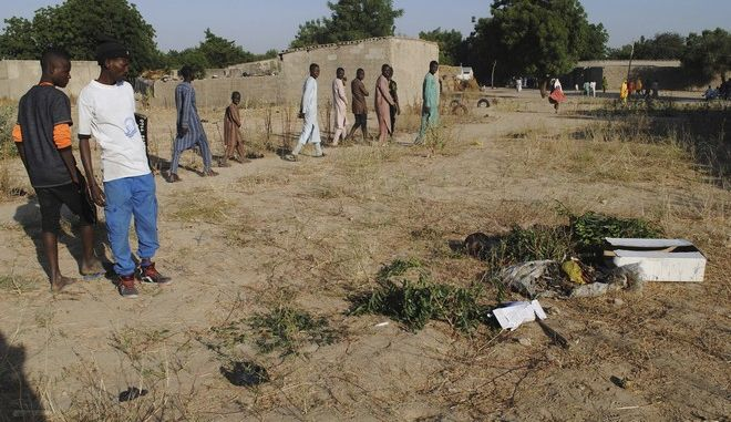 People gathered at the site of a suicide attack in Maiduguri, Nigeria, Thursday, Nov. 16, 2017. Police in Nigeria say four suicide bombers detonated explosives in the Borno state capital and killed more than a dozen people and wounded others. (AP Photo/Jossy Ola)