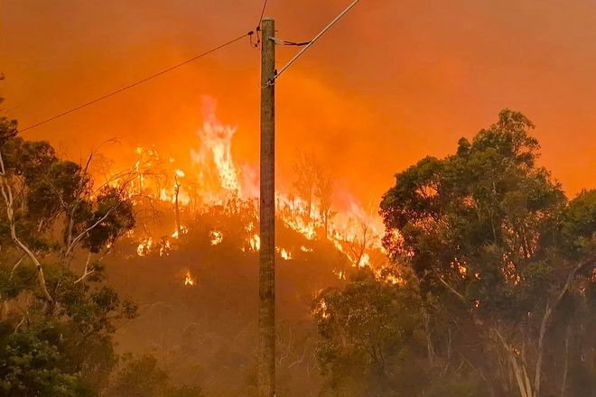 In this photo provided by Department of Fire and Emergency Services, fire burns on a hill at Wooroloo, near Perth, Australia, Monday, Feb. 1, 2021. An out-of-control wildfire burning northeast of the Australian west coast city of Perth has destroyed an estimated 30 homes and was threatening more Tuesday, with many locals across the region told it is too late to leave. (Brenden Scott/DFES via AP)