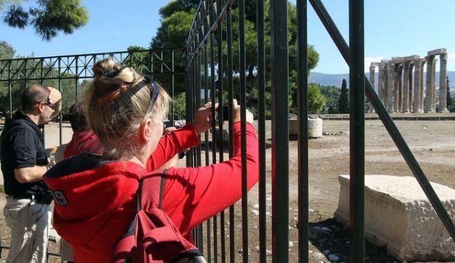 Τουρίστες φωτογραφίζουν πίσω από τα κλειστά κάγκελα τον αρχαιολογικό χώρο του Ολυμπίου Διός, Αθήνα Τετάρτη 12 Οκτωβρίου 2011. Οι εργαζόμενοι του Υπουργείου Πολιτισμού έχουν προκηρύξει 48ωρη απεργία με αποτέλεσμα οι αρχαιολογικοί χώροι να είναι κλειστοί. ΑΠΕ-ΜΠΕ/ΑΠΕ-ΜΠΕ/ΟΡΕΣΤΗΣ ΠΑΝΑΓΙΩΤΟΥ