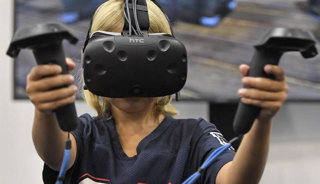 A young gamer plays with a virtual reality mask at the international game fair 'SPIEL' in Essen, Germany, Thursday, Oct. 26, 2017. Around 1100 exhibitors from around 50 nations attend the annual four-day game fair. (AP Photo/Martin Meissner)