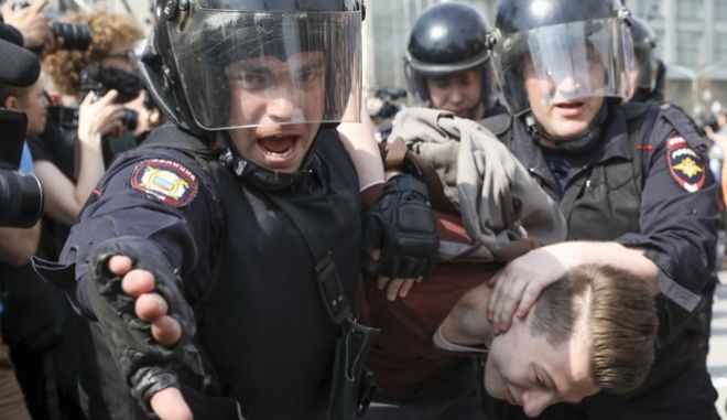 Αστυνομικός κρατά διαδηλωτή σε διαδήλωση κατά του προέδρου Βλαντιμίρ Πούτιν στη Μόσχα, το Σάββατο 5 Μαΐου. Η αστυνομία συνέλαβε και τον διοργανωτή της Αλεξέι Ναβάλι