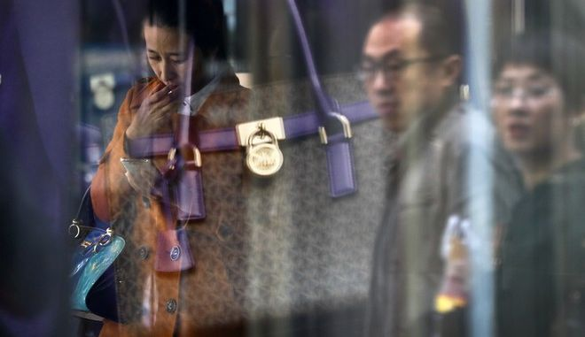 A couple walk by a fashion bag reflected on a woman checking on her smartphone outside a fashion boutique at the capital city's popular shopping mall in Beijing, Thursday, Oct. 19, 2017. China's economic growth stayed relatively stable in the latest quarter, buoyed by strength in retail spending and exports, giving the ruling Communist Party a boost as it prepares to appoint President Xi Jinping to a new term as leader.(AP Photo/Andy Wong)