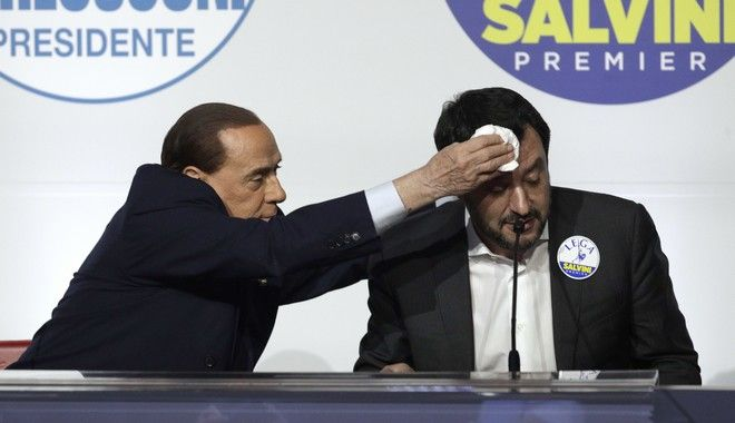 Forza Italia's Silvio Berlusconi, left, whipes the forehead of League's Matteo Salvini at a media event for center-right leaders ahead of the March 4 general elections, in Rome, Thursday, March 1, 2018. (AP Photo/Andrew Medichini)