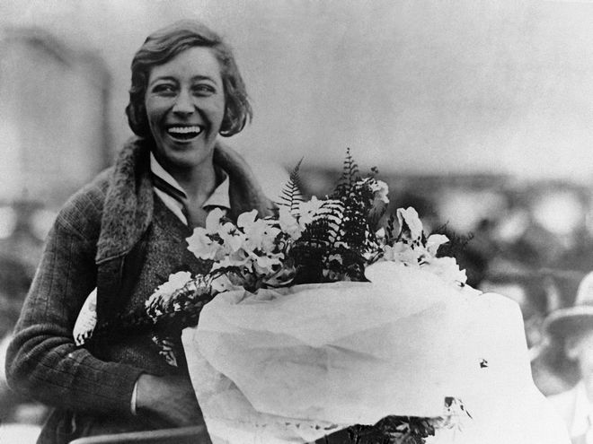Female pilot Amy Johnson smiling and holding a the bouquet she was presented with at the City hall in Brisbane, Australia around June 24, 1930. Johnson crashed of her arrival at Brisbane, but was unhurt. (AP Photo)