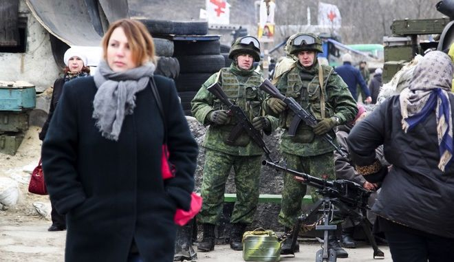 People cross a check point guarded by separatist rebels between Ukrainian government controlled and rebel controlled areas at the village of Luhanska, Ukraine, Tuesday, March 7, 2017. Russia on Tuesday rejected allegations that it sponsors terrorism by funneling arms and money to separatist rebels in eastern Ukraine. (AP Photo/Alexander Ermochenko)