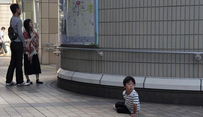A family looks at a map at Shinagawa station in Tokyo, Sunday, Oct. 1, 2017. (AP Photo/Shizuo Kambayashi)