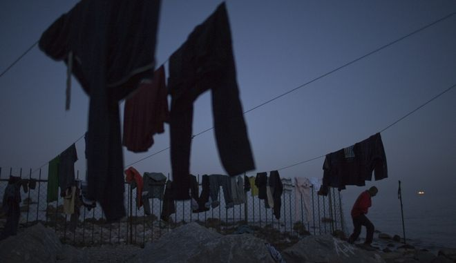 A man walk next clothes hung on a rope to dry in a camp set up by volunteers hosting around 250 migrants near the port of Mytilini, in the Greek island of Lesbos, on Friday, April 15, 2016. Pope Francis will visit the island Saturday joined by Ecumenical Patriarch Bartholomew and the head of the Orthodox Church of Greece, Athens Archbishop Ieronymos II, a mission human rights groups hope will highlight the plight of refugees who fled their war-ravaged homes only to be denied entry to Europe. (AP Photo/Petros Giannakouris)