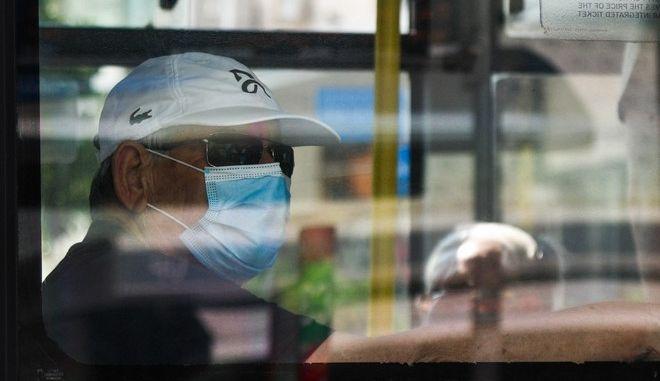Άντρας με μάσκα σε λεωφορείο (φωτογραφία αρχείου)