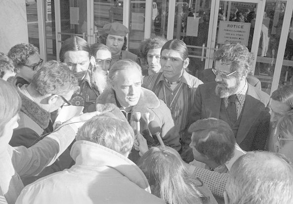 (Original Caption) Actor Marlon Brando (center) was mobbed by reporters when he emerged from the federal court house in St. Paul, Minnesota, where Indian leaders Russell Means (left) and Dennis Banks (right) are on trial for their involvement in the 71 day takeover of Wounded Knee, South Dakota.