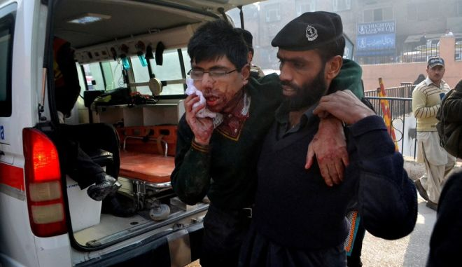 A hospital security guard helps a student injured in the shootout at a school under attack by Taliban gunmen in Peshawar, Pakistan,Tuesday, Dec. 16, 2014. Taliban gunmen stormed a military school in the northwestern Pakistani city, killing and wounding dozens, officials said, in the latest militant violence to hit the already troubled region. (AP Photo/Mohammad Sajjad)