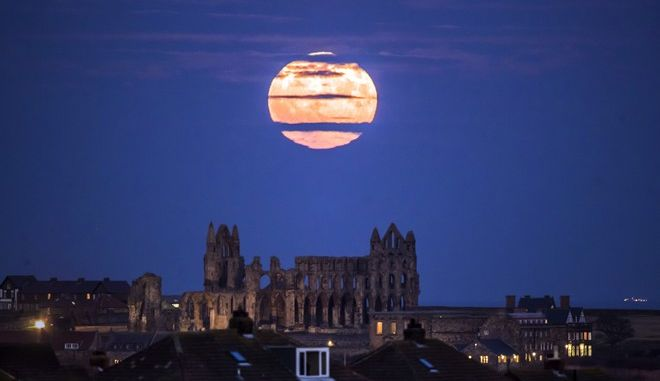 The Supermoon rises above Whitby Abbey in Whitby, north east England, Sunday Dec. 3, 2017. The Dec. 3 full moon will be the first of three consecutive supermoons. (Danny Lawson/PA via AP)