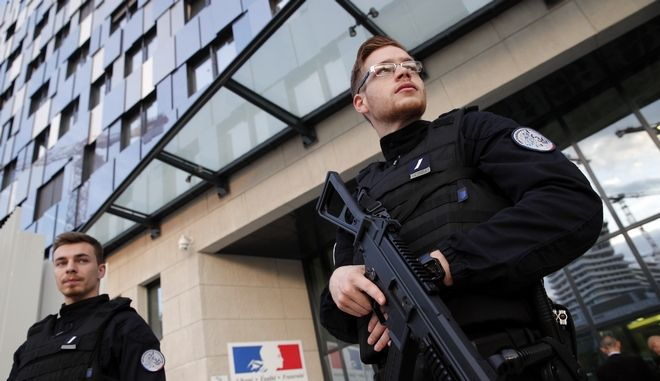 Policemen stand guard in front of the new Paris police headquarters during its inauguration, Thursday Oct. 19, 2017. (AP Photo/Christophe Ena)