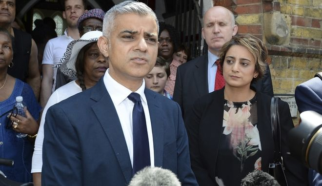 Mayor of London Sadiq Khan makes a statement outside St Clements Church, near to Grenfell Tower in west London, Sunday June 18, 2017. Khan attended a church service near the ruined London high-rise apartment building where at least 58 people perished. The mayor and his wife Saadiya, right, joined the congregation Sunday at St. Clement's Church near Grenfell Tower. (John Stillwell/PA via AP)