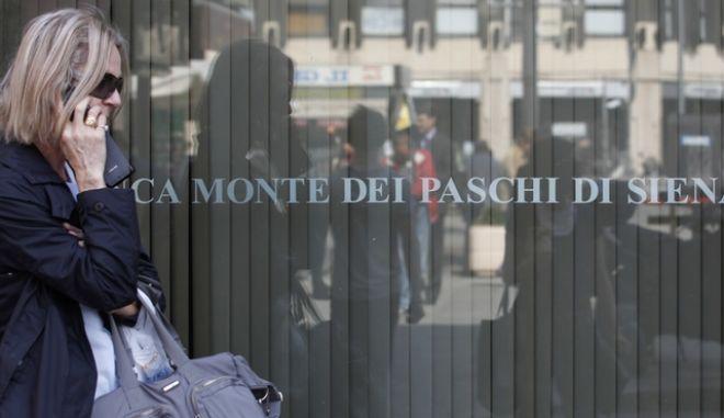 Γυναίκα περνάει μπροστά από ιταλική τράπεζα