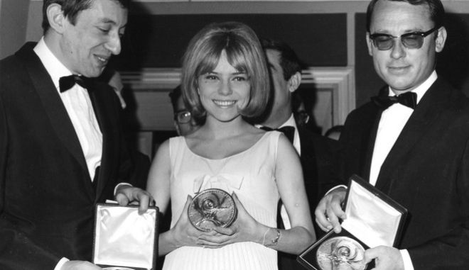 "18-year-old French singer France Gall, singing for Luxembourg in the Eurovision Song Contest, proudly presents her winning medal for performing the Serge Gainsbourg, left, song ""Poupee de Cire, Poupee de Son"" (Wax Doll, Rag Doll) with orchestra director Alain Gorauguer, right, after beeing awarded in Naples, Italy, March 20, 1965. (AP Photo/Guilio Broglio)"