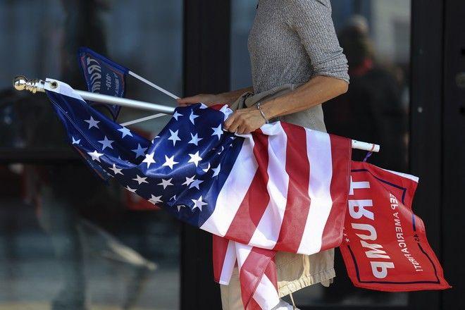 Γυναίκα με τη σημαία των ΗΠΑ περιμένει για να ψηφίσει στις αμερικανικές εκλογές