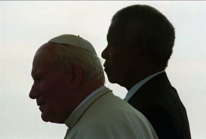 Pope John Paul II and South African President Nelson Mandela stand for national anthems after the Pontiff's arrival to Johannesburg Saturday, September 16, 1995. The visit marks the Pope's first official trip to South Africa. (AP Photo/John Moore)