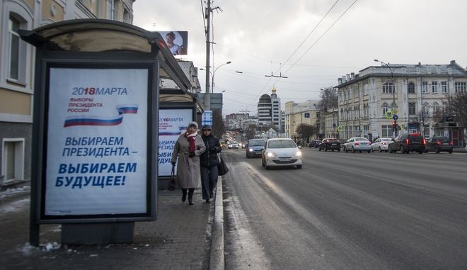 """People walk through a street with an election poster that reads: """"Choose President - Choose Future!"""" in Yekaterinburg, Russia, Saturday, March 17, 2018. Just like in any other city or town in Russia, thousands of state employees in Yekaterinburg are under pressure from the management to come out to vote in Sunday's presidential election in line with the Kremlin's efforts to boost the turnout. (AP Photo/Nataliya Vasilyeva)"""