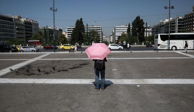 Ένας άνδρας κρατά ομπρέλα στο Μνημείο του Άγνωστου Στρατιώτη