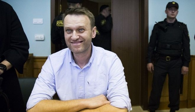 Russian opposition leader Alexei Navalny smiles during a hearing on his appeal in a court in Moscow, Russia, Friday, June 16, 2017. Navalny was detained outside his home in Moscow before the protest and was sentenced to 30 days in jail for staging an unsanctioned rally. (AP Photo/Alexander Zemlianichenko)