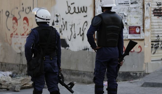 "Riot police patrol on the lookout for protesters against Saudi Arabia's execution of Shiite cleric Sheikh Nimr al-Nimr in Daih, Bahrain, a largely Shiite suburb of the capital, Monday, Jan. 4, 2016. Graffiti on the wall reads, ""Down, Hamad, forever,"" near pictures of people who died in previous unrest. Allies of Saudi Arabia, including the monarchy in neighboring Bahrain, began scaling down their diplomatic ties to Iran in the wake of the ransacking of Saudi diplomatic missions in Iran that followed al-Nimr's execution. (AP Photo/Hasan Jamali)"