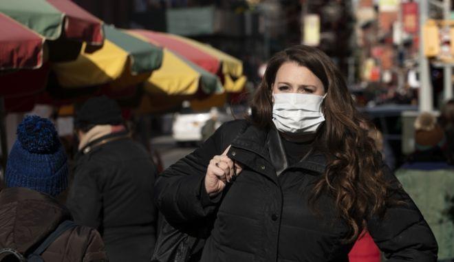 Γυναίκα φοράει μάσκα για να προστατευθεί από τον Κοροναϊό