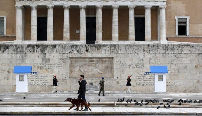 Άνδρας κάνει βόλτα τον σκύλο του μπροστά από την ελληνική Βουλή